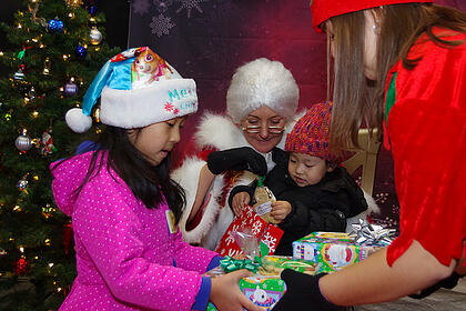 Young girl and boy receiving gifts from an elf while sitting with Mrs. Claus