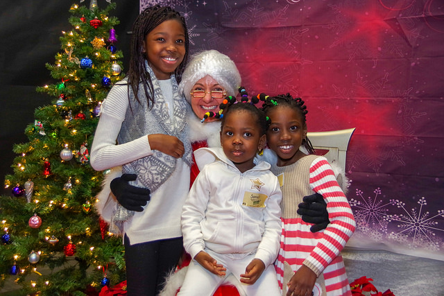 Three young girls posing in front of a Christmas Tree with Mrs. Claus