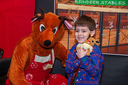 Young boy hugging a stuffed animal and posting with someone in a reindeer costume