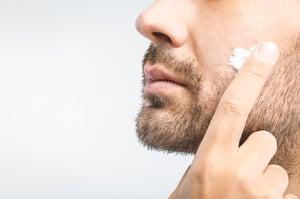man applying facial serum