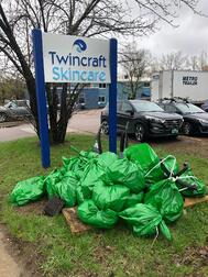 Piles of green trash bags next to Twincraft Skincare sign